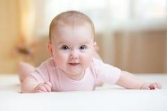 Mensonge de port de bébé mignon sur le ventre dans la chambre à coucher Images libres de droits