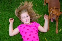Mensonge de sourire de belle d'enfant fille blonde d'enfants sur l'herbe Images stock