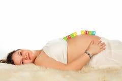 Mensonge de sourire enceinte de femme Photographie stock