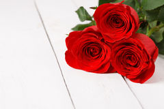Mensonge de trois roses rouges sur la table blanche Image stock