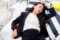 Mensonge fatigué de sommeil d'exécutif sur un sofa dans le salon à la maison après travail Images stock