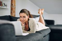 Mensonge femelle assez jeune sur le sofa avec un ordinateur portable photo stock