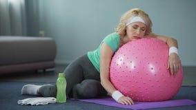 Mensonge femelle mûr épuisé sur la boule de forme physique, détendant après séance d'entraînement active banque de vidéos
