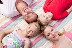 Mensonge gai de sommeil de famille sur l'herbe photo stock