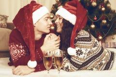 Mensonge heureux de couples près d'arbre et de décoration de Noël à la maison Vacances d'hiver et concept d'amour jaune modifié l Photo libre de droits