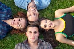 Mensonge heureux de quatre adolescents tête à tête Images libres de droits