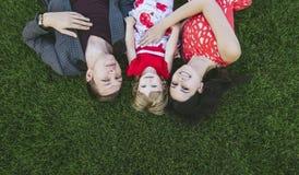 Mensonge heureux et beau de famille, de maman, de papa et de fille sur le vert Images libres de droits