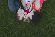Mensonge heureux et beau de famille, de maman, de papa et de fille sur le vert Photos stock