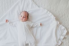 Mensonge nouveau-né sur son dos sur le lit Images stock