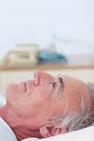 Mensonge patient aîné sur un bâti d'hôpital images stock