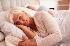 Mensonge supérieur inquiété de femme éveillé dans le lit photos stock