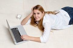 Mensonge travaillant de femme sur le plancher Photographie stock libre de droits