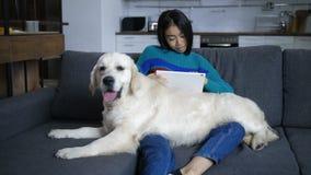 Mensonges de chien sur des genoux de comprimé de observation de propriétaire indien banque de vidéos
