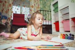 Mensonges de petite fille sur le plancher de chambre à coucher et la photo de peinture photo libre de droits