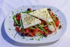 Mensonges grecs de salade dans un plat avec du feta et des olives arrosés avec l'origan Images libres de droits