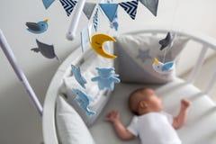 Mensonges nouveau-nés dans le lit blanc rond avec le mobile Photos stock