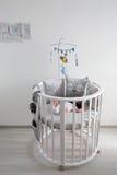 Mensonges nouveau-nés dans le lit blanc rond avec le mobile Image libre de droits