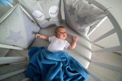Mensonges nouveau-nés dans le lit blanc rond avec le mobile Photographie stock
