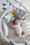 Mensonges nouveau-nés dans le lit blanc rond avec le mobile Image stock