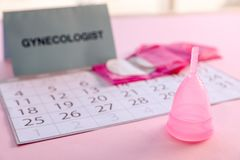 Menstrual cup and calendar on table. Gynecological care royalty free stock images
