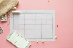 Menstrual cycle. Calendar for the month with marks and a mobile application on the smartphone screen. Contraceptive and pain pills on the background stock photos