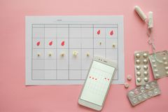 Menstrual cycle. Calendar for the month with marks and a mobile application on the smartphone screen. Tablets and toiletries on a pink background stock photos