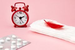 Menstrual pads, blood period calendar, clocks and pills. White pharmaceutical tablets. Menstruation period pain protection. Contra Stock Photography