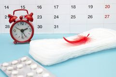 Menstrual pads, blood period calendar, clocks and pills. White pharmaceutical tablets. Menstrual period pain protection. Contracep stock photography
