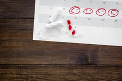 Menstrual period concept. Menstruation calendar with hygienic tampons and pills on dark wooden background top view space royalty free stock photo