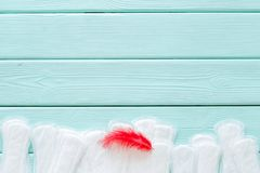 Menstrual period concept with sanitary pads and red feather on mint green wooden background top view copy space stock photography