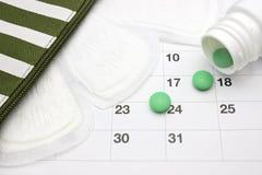 Menstruatiestootkussens, menstruele kalender en groene pillen Groene farmaceutische tabletten die uit een witte pillenfles morsen stock afbeeldingen