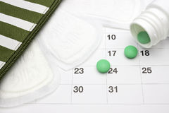 Menstruation pads, menstrual calendar and green pills. Green pharmaceutical tablets spilling out of a white pill bottle. Menstrual stock images