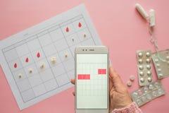 Menstruele cyclus Kalender voor de maand met tekens en een mobiele toepassing op het smartphonescherm royalty-vrije stock afbeeldingen