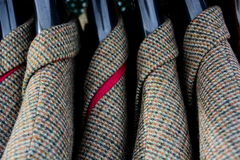 Menswear tweed jackets. A collection of tweed checked leisure wear jackets hanging on a rack in a shop Royalty Free Stock Images
