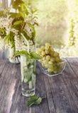 Menta de agua del Detox, jugo de uva e hielo en un vidrio en un fondo de un ramo de cerezas y de uvas en un día soleado La vertic Fotografía de archivo