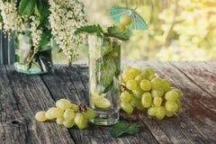 Menta de agua del Detox, jugo de uva e hielo en un vidrio en un fondo de un ramo de cereza y de uvas en un día soleado Foto de archivo libre de regalías