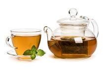 Menta fresca y té verde en una taza y una tetera del vidrio Imagen de archivo libre de regalías
