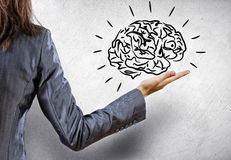 Mental ability. Rear view of businesswoman holding human brain in palm Royalty Free Stock Image