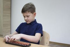 Mental arithmetic school. Japanese abacus. Mental arithmetic school. Boy counts with abacus in `soroban` class. Japanese abacus. Concept of back to school Stock Images