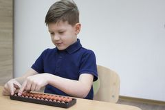 Mental arithmetic school. Japanese abacus. Mental arithmetic school. Boy counts with abacus in `soroban` class. Japanese abacus. Concept of back to school Royalty Free Stock Image