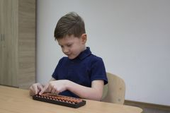 Mental arithmetic school. Japanese abacus. Mental arithmetic school. Boy counts with abacus in `soroban` class. Japanese abacus. Concept of back to school Royalty Free Stock Images