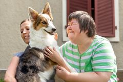 Mental disabled woman in front of a house is holding her dog stock images