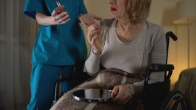 Mental disorder woman applying lipstick and nurse taking makeup away, lost time. Stock footage stock video footage