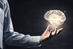 Mental health. Close up of businessman holding digital image of brain in palm Stock Photo