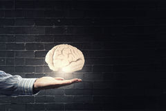 Mental health. Close up of businessman holding digital image of brain in palm Royalty Free Stock Photo