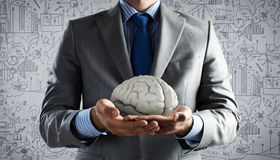 Mental health. Close up of businessman holding human brain in palms Stock Photo