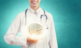 Mental health. Close up of female doctor with stethoscope and brain in hands Stock Image