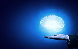Mental health. Close up of human hand holding brain on blue background Royalty Free Stock Images