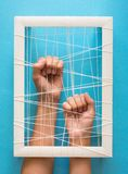 Mental health concept. Women`s hands try to break the fetters on blue background Stock Photography