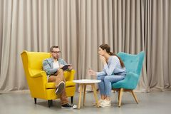 Mental Health Consultation. Full length portrait of young women talking to mature psychologist in therapy session sitting on design chairs against drapery, copy royalty free stock images